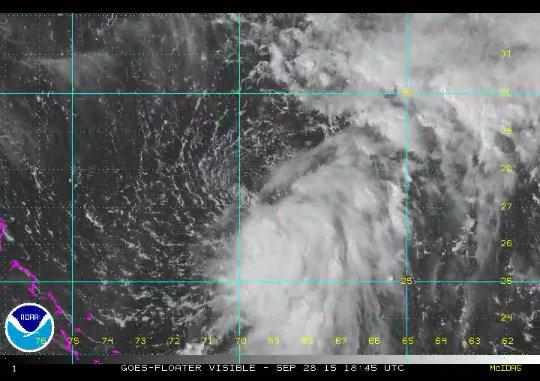Tropical Depression 11 in the Caribbean earlier this afternoon, remaining weak with a partially exposed circulation.